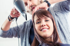 Hairdresser blow dry hair in shop Royalty Free Stock Photos