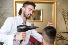 Hairdresser Blow Dry Man's Hair In Shop Royalty Free Stock Photos