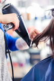 Hairdresser blow dry woman hair in shop Stock Photography
