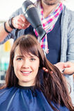 Hairdresser blow dry woman hair Stock Images