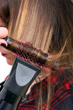 Hairdresser blow-drying a clients hair Stock Photos