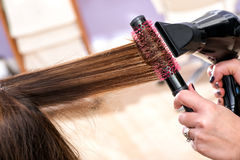 Hairdresser blow drying long brown hair Stock Photography