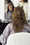 Hairdresser blow-drying woman's hair with hair dryer in salon, rear view, reflection in mirror Royalty Free Stock Photography