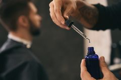 Hairdresser with bottle of beard serum in barbershop. Professional shaving. Service stock photos