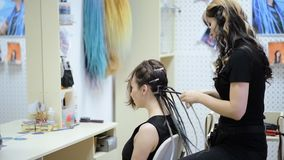 Girl hairdresser weaves dreadlocks client in the salon. Hairdresser braids dreadlocks girl in the salon stock video