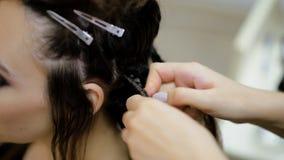 Girl hairdresser weaves dreadlocks client in the salon. Hairdresser braids dreadlocks girl in the salon stock video footage