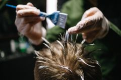 Hairdresser with a brush to apply hair dye. Coloring in the barber shop royalty free stock images