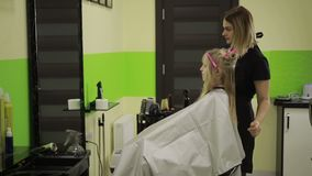 Hairdresser brushing girl`s hair in beauty salon. stock video footage