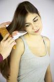 Hairdresser brushing long hair. Brunette female model getting hair brushed by hairdresser happy Royalty Free Stock Images