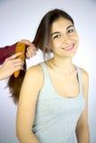Hairdresser brushing long hair of female model. Young girl smiling while hairdresser brushes her long silky hair Stock Images