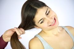 Hairdresser brushing long hair of female model. Young girl smiling while hairdresser brushes her long silky hair Royalty Free Stock Images