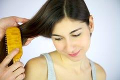 Hairdresser brushing long hair of female model. Young girl smiling while hairdresser brushes her long silky hair Stock Image