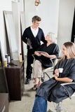 Hairdresser With Client's In Salon Stock Photography