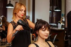 Hairdresser and client in the salon, beauty salon and hair care royalty free stock photography