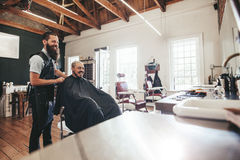 Hairdresser with client sitting at salon and smiling. Man getting haircut at barber shop stock image