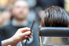 Hairdresser coiffeur makes hairstyle with electric trimmer and c Royalty Free Stock Images