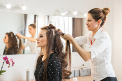 Hairdresser coiffeur makes hairstyle. Hairdresser coiffeur makes hairstyle for young woman royalty free stock image