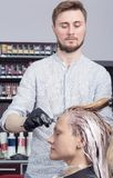 A hairdresser coloring hair of a blonde female client Royalty Free Stock Image