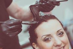 Hairdresser coloring hair Stock Photos