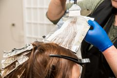 Hairdresser coloring hair in studio. highlighting or coloring of red hair.  stock photography