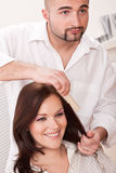 Hairdresser comb customer at salon Stock Photography