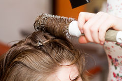 Hairdresser comb female client`s wet hair Stock Photography