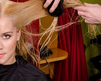 Hairdresser combing blond hair Royalty Free Stock Photo