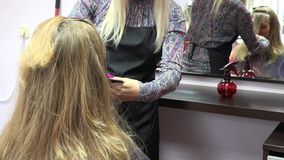 Hairdresser combing female customer hair in front of mirror. Focus change. 4K stock footage