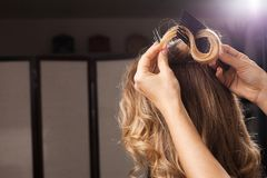 Hairdresser combing a hair curl stock image