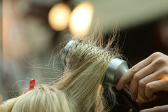Hairdresser combing hair by hairbrush and hair dryer Stock Photography