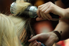 Hairdresser combing hair by hairbrush and hair dryer Royalty Free Stock Photography