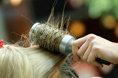 Hairdresser combing hair by hairbrush and hair dryer Royalty Free Stock Photo