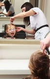 Hairdresser combing hair little girl child in hairdressing beauty salon Royalty Free Stock Photos