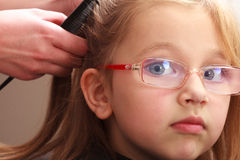 Hairdresser combing hair little girl child in hairdressing beauty salon Royalty Free Stock Image