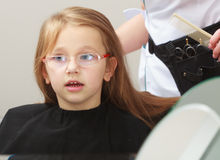 Hairdresser combing hair little girl child in hairdressing beauty salon Stock Photography