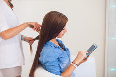 Hairdresser combing hair woman with mobile phone in hairdressing Royalty Free Stock Image
