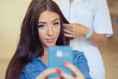 Hairdresser combing hair woman with mobile phone in hairdressing Royalty Free Stock Images