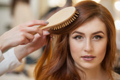 Hairdresser combing her long, red hair of his client in the beauty salon. Royalty Free Stock Image