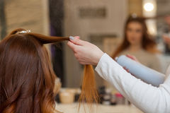 Hairdresser combing her long, red hair of his client and sprinkles hairspray in a beauty salon. Professional hair care and creating hairstyles stock photos