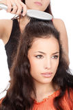 Hairdresser combing woman's long black hair Royalty Free Stock Photo