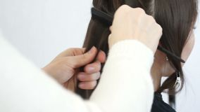 Hairdresser combs a strand of hair. With a plastic comb stock video footage