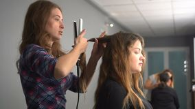 Hairdresser curling hair to brown hair girl in beauty salon stock video footage