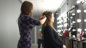 Hairdresser curling hair to brown hair girl in beauty salon stock footage