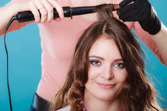 Hairdresser curling woman hair with iron curler. Stock Photos