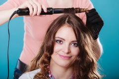 Hairdresser curling woman hair with iron curler. Stock Image