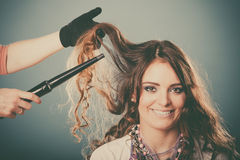 Hairdresser curling woman hair with iron curler. Stock Photography