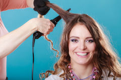 Hairdresser curling woman hair with iron curler. Royalty Free Stock Photo