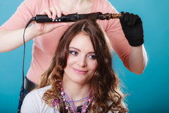 Hairdresser curling woman hair with iron curler. Hairdresser curling women hair with electric iron curler tong. Hairstylist making girl hairstyle. Attractive Stock Photography