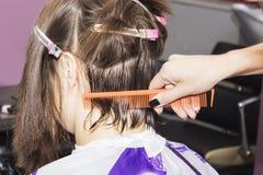 Hairdresser cut brown hair in the hands of the scissors and comb Imágenes de archivo libres de regalías