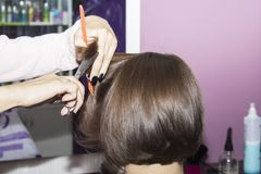 Hairdresser cut brown hair in the hands of the scissors and comb Fotografía de archivo